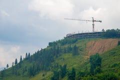 在小山顶的建筑用起重机大厦 免版税库存照片