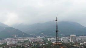 在小山顶部的云彩,依靠山的城市大厦 全景台山,泰安城市 影视素材