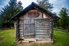 在小山顶部的老小木房子在反对剧烈的天空背景的森林里 免版税库存图片