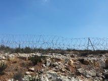 在小山,巴勒斯坦占领的标志的铁丝网 免版税库存照片