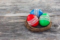 在小巢的五颜六色的复活节彩蛋在木背景 免版税库存照片