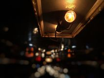 在小巴屋顶的电灯泡  城市点燃晚上场面 免版税库存照片