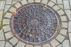 在小径的圆的人孔盖 免版税库存照片