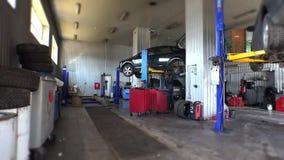 在小服务站和技工修理一汽车举的两辆汽车 股票视频