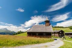 在小村庄铺石渣导致木教会的路在阿尔卑斯 免版税库存图片