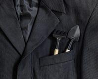 在小条纹衣领口袋袖子的人` s黑暗的夹克在口袋铁锹和犁耙在木把柄染黑 图库摄影
