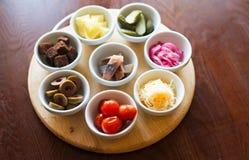 在小板材的开胃菜在棕色背景 免版税库存图片