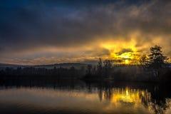 在小池塘的有薄雾的黄色和蓝色日落在捷克Moravian高地 免版税库存图片