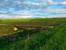 在小河上的桥梁铁老混凝土,在领域中的一个被放弃的地方,与多云天空 免版税库存图片