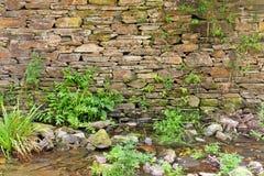 在小河的古老石墙 库存图片