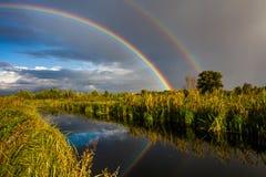 在小河的惊人的双重彩虹 免版税库存照片