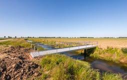 在小河的最近被修建的现代铝桥梁 库存照片