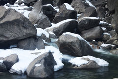在小河的积雪的岩石 库存照片
