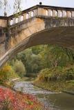 在小河的老石人行桥在与秋天颜色的秋天 库存图片