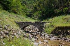 在小河的老石桥梁 图库摄影