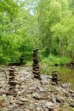 在小河附近向金字塔扔石头 免版税库存图片
