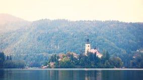 在小海岛上的老教会在有流动在watter,流血的湖斯洛文尼亚的长平底船的湖中间 免版税图库摄影