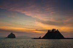 在小海岛的日落剪影的 免版税库存图片