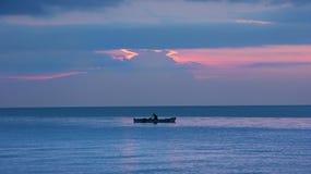 在小渔船的渔夫剪影在黄昏的海洋与橙色日落 免版税库存照片