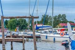 在小游艇船坞停泊的几条游艇 多云早晨 免版税库存照片