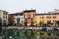 在小游艇船坞口岸的Desenzano del加尔达景色,与小船的港口视图,有在修造的威尼斯式样式的好的看法 免版税图库摄影