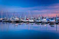 在小游艇船坞小行政区的,巴尔的摩,马里兰的暮色反射 免版税库存照片