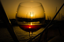 在小游艇船坞的日落有美好的杯的酒 免版税库存照片