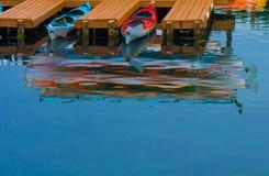 在小游艇船坞水波纹反映的皮船 库存图片