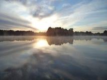在小湖的有薄雾的日出 库存图片