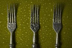 在小滴的叉子在色的背景的水 图库摄影