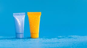 在小滴的抽象五颜六色的化妆管水 刷新的卫生学医学供应,橙色蓝色颜色塑料 免版税库存照片