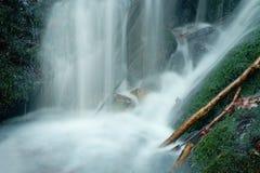 在小瀑布下的喷水在山小河,水落在生苔冰砾 浪花在水平和石渣mi创造 免版税库存照片