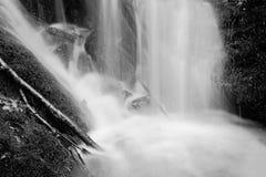 在小瀑布下的喷水在山小河,水落在生苔冰砾 浪花在水平和石渣mi创造 库存图片