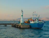 在小灯塔附近的蓝色小船在王子Islands 库存照片