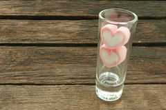 在小狭窄的玻璃的可爱的桃红色心脏蛋白软糖在老深褐色的板条 库存图片