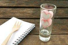 在小狭窄的玻璃的可爱的桃红色心脏蛋白软糖在老深褐色的板条 免版税图库摄影