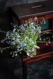 在小玻璃瓶子的勿忘草的花束在板凳,黑暗的背景 库存图片