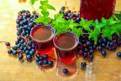在小玻璃的自创酒用在桌上的黑当前莓果 免版税图库摄影