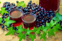 在小玻璃的自创酒用在桌上的黑当前莓果 免版税库存图片