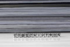 在小珠的订阅与在背景中堆积的杂志 免版税库存照片