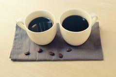 在小白色杯子的两份浓咖啡咖啡在灰色餐巾 图库摄影