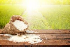在小粗麻布大袋的白米在木桌上 免版税库存照片
