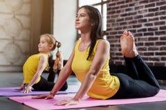 在小组瑜伽训练期间,年轻穿同一件运动服的母亲和她的女儿做眼镜王蛇摆在 免版税库存照片