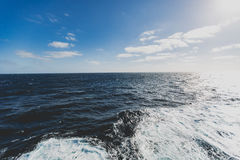 在小船后挥动,当巡航通过明亮的太阳光的时海洋 库存照片
