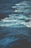 在小船后挥动,当巡航通过明亮的太阳光的时海洋 免版税图库摄影