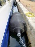 在小船和码头之间的气动力学的防御者 库存照片
