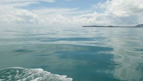 在小船和镇静海洋以后的小泡沫似的蓝色波浪在阴天 田园诗热带waterscape 天空被反射  股票录像
