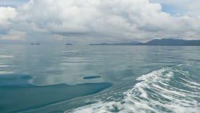在小船和镇静海洋以后的小泡沫似的蓝色波浪在阴天 田园诗热带waterscape 天空被反射  股票视频