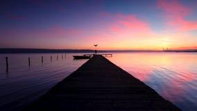 在小船坞和小船在湖,日落的空中寄生虫飞行 股票录像