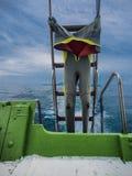 在小船垂悬的潜水衣 免版税图库摄影